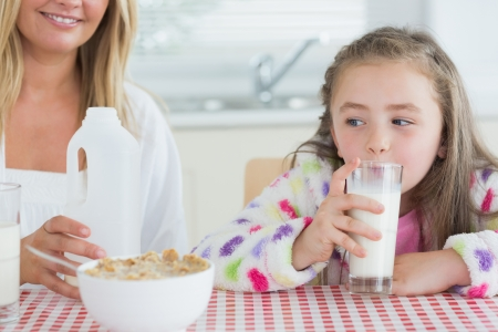 Little girl drinking milk at the kitchen  photo