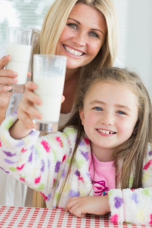 Mother and daughter raising milk glasses in kitchen photo