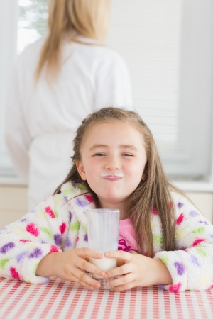 children breakfast: Little girl with milk moustache after drinking glass of milk Stock Photo