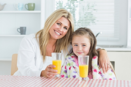 Woman and little girl sitting at the kitchen having a glass of juice at breakfast photo