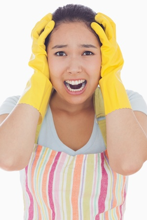 out of context: Stressed woman wearing rubber gloves and apron with her hands on head and screaming