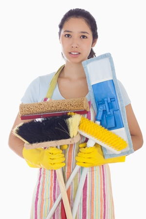 Frowning woman in apron and rubber gloves holding brushes and mops photo