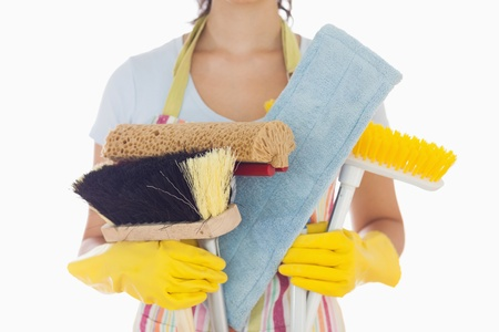 cleaning service: Woman in apron and rubber gloves holding brushes and mops Stock Photo