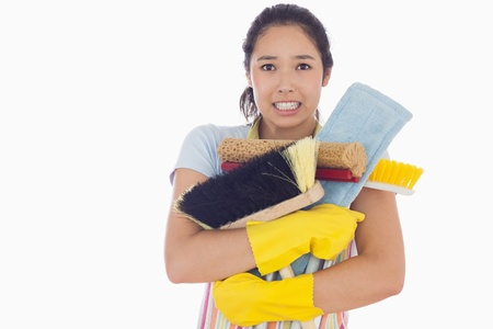 Woman holding mops and brushes with them nearly falling photo