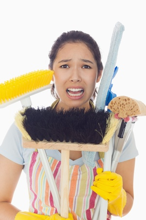 Distressed young woman in apron and rubber gloves holding cleaning tools photo