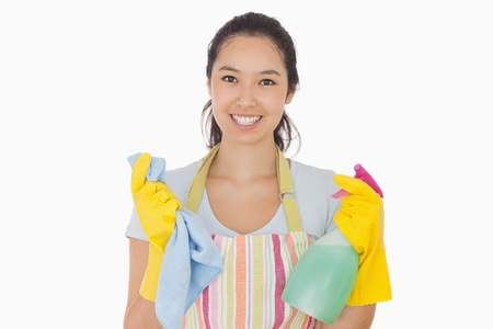 out of context: Smiling woman holding cloth and spray bottle in apron and rubber gloves