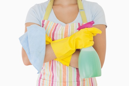 Woman holding window cleaner and rag wearing apron and rubber gloves photo