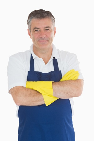 out of context: Man with arms crossed in blue apron wearing rubber gloves