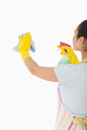 the window: Woman cleaning wall with cloth and spray bottle