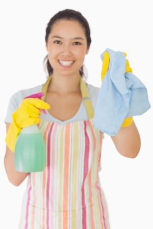 spr�hflasche: L�chelnde junge Frau h�lt Lappen und Spr�hflasche in Sch�rze und Gummihandschuhe Lizenzfreie Bilder