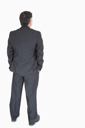 detras de: Hombre de negocios de nuevo con las manos en los bolsillos