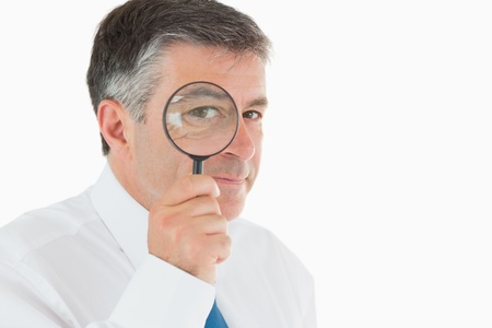 Businessman looking through small magnifying glass and smiling photo