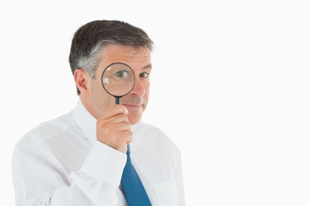 Smiling businessman looking through magnifying glass photo