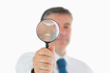 Smiling businessman holding up magnifying glass photo