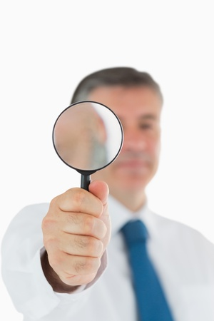 Businessman holding up a magnifying glass photo