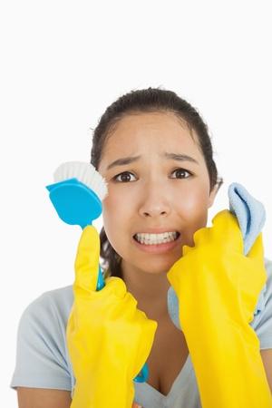 fregando: Estresado mujer sosteniendo fregado del cepillo y trapo con guantes de goma Foto de archivo