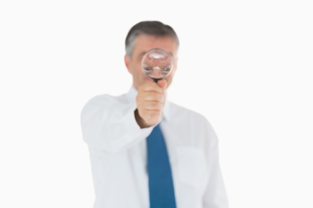 Businessman in shirt and tie behind magnifying glass photo