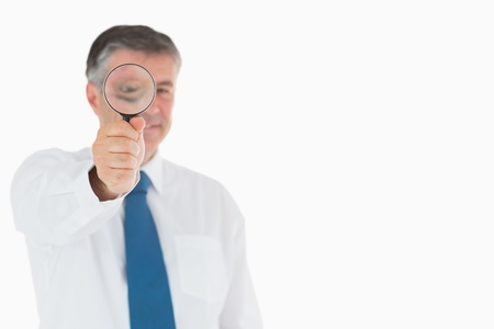 investigating: Smiling businessman in shirt and tie using magnifying glass