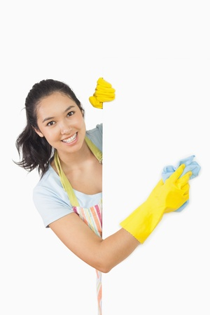 cleaning service: Smiling woman in apron and rubber gloves cleaning white surface