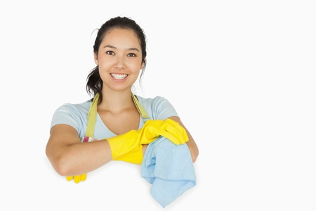 cleaning service: Smiling woman in apron and rubber gloves leaning on white surface with a rag