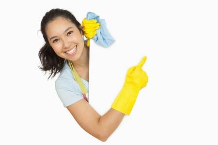 out of context: Woman in rubber gloves and apron pointing to the white surface she is behind