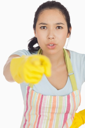 accusing: Accusing woman in apron and rubber gloves pointing ahead