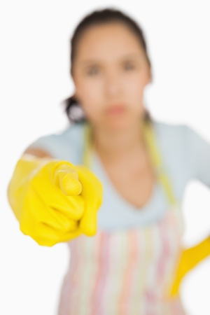 Woman in apron and gloves pointing accusingly ahead Stock Photo - 16067784