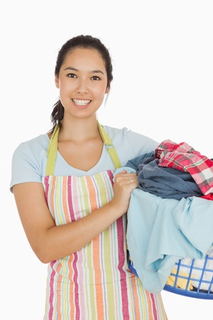 Smiling woman holding blue laundry basket with dirty laundry  photo