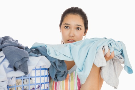 out of context: Frowning young woman taking out the dirty laundry from the basket
