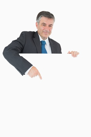 Happy businessman pointing at the white board that he is holding photo