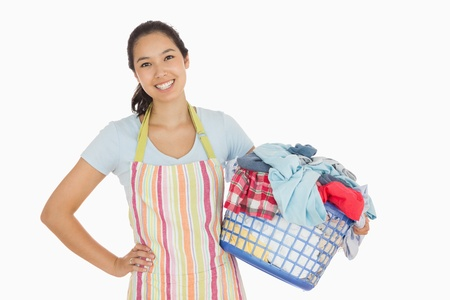 laundry basket: Happy woman in apron holding full laundry basket
