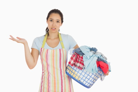 out of context: Puzzled look young woman holding laundry basket full of dirty laundry with wrinkled hands
