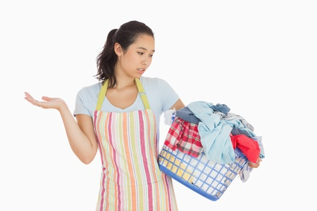 quizzical: Quizzical looking young woman in apron looking at basket full of dirty laundry