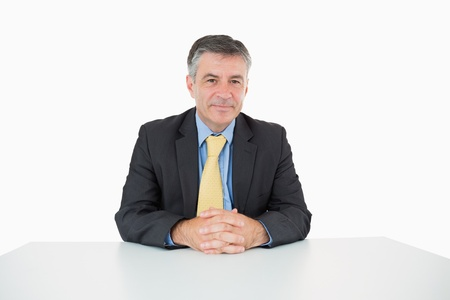 Well-dressed man sitting at his desk on white background photo