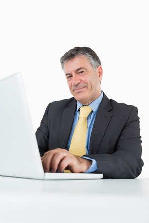 Businessman typing on laptop at his desk photo