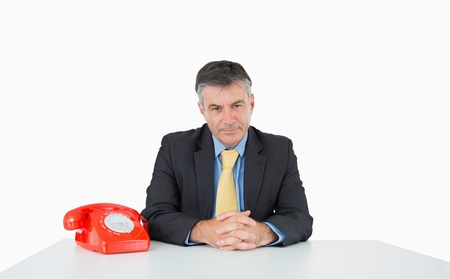 Calm man sitting at his desk with a phone on a white background photo
