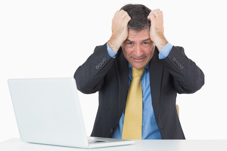 Troubled man sitting at his desk with a laptop on a white background photo