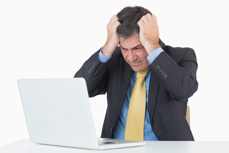 agitated: Anxious businessman sitting at his desk with a laptop on a white background