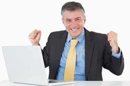Succesful businessman sitting at his desk with his laptop on white background photo