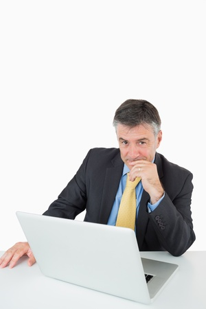 Smiling man sitting at his desk with a laptop on a white background photo