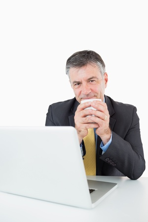 Smiling man with a laptop is drinking coffee at his desk in a white background photo