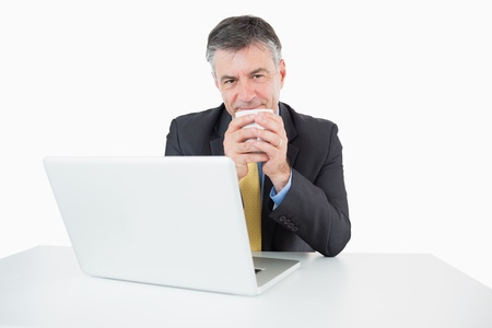 Happy man with a laptop is drinking coffee at his desk on a white background photo