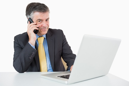 Happy businessman phoning while typing on laptop on a white background photo