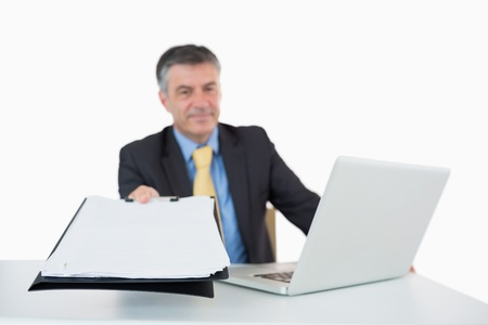 Man holding a clipboard out with a laptop photo