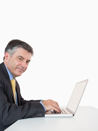 Happy man typing on his laptop on his desk in a white background photo