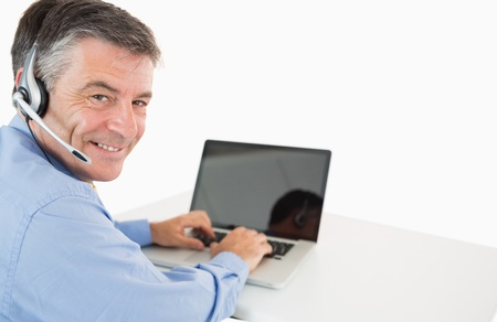Smiling businessman with headset working on laptop at desk photo