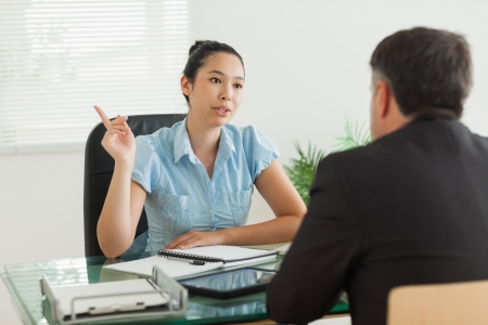 Businesswoman talking with a man in her office photo