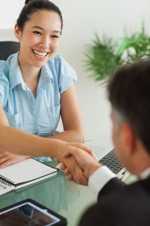 Happy businesswoman shaking man's hand in her office photo