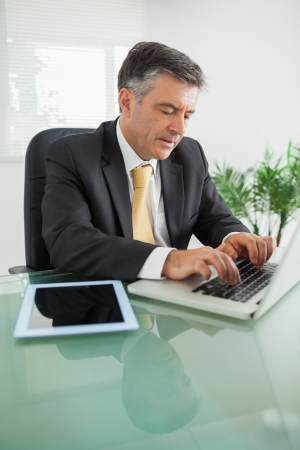Concentrated business man working on laptop on a table in an office  photo