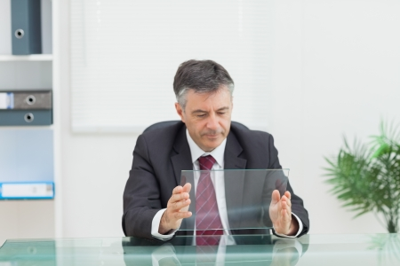 Business man holding a virtual screen on his desk in his office  photo